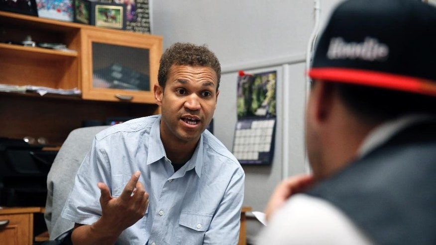 """FILE - In this April 22, 2015 file photo, Aurora movie theater shooting survivor Marcus Weaver counsels a client at New Genesis Transitional Community for the Homeless, which Weaver co-manages, in Denver. Weaver has talked openly for years about forgiving the man who shot him, killed his friend and caused untold suffering. As a Christian who is philosophically opposed to capital punishment, he said, finding forgiveness was """"a no-brainer."""" But by the time James Holmes was convicted in the chilling 2012 attack on a Colorado movie theater, Weaver had changed his mind. """"I feel the sentence that he may get, which is the death penalty, is the only penalty that fits the crime that he committed that night,"""" Weaver said. (AP Photo/Brennan Linsley, file)"""