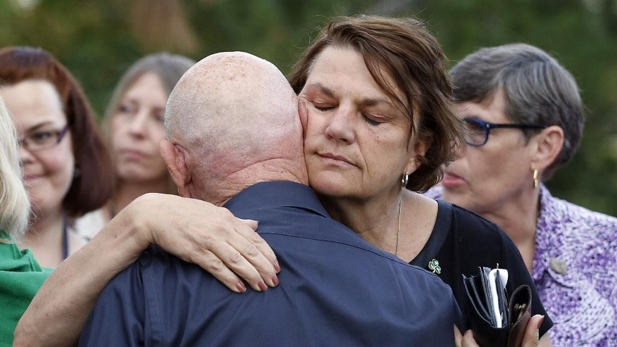 Dave Hoover, center left, whose nephew A.J. Boik was killed in the 2012 Aurora movie theatre attack, embraces Caren Teves, whose son Alex was also killed, as Teves' husband Tom, left holds an umbrella, after a jury failed to agree on whether theater shooter James Holmes should get the death penalty Friday, Aug. 7, 2015, in Centennial, Colo. Holmes will be sentenced to life in prison without parole. (AP Photo/Brennan Linsley)