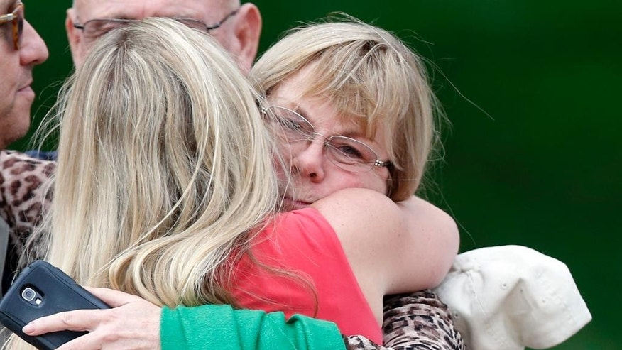 Dave Hoover, center left, whose son A.J. Boik was killed in the 2012 Aurora movie theatre attack, embraces Caren Teves, whose son Alex was also killed, as Teves' husband Tom, left holds an umbrella, after a jury failed to agree on whether theater shooter James Holmes should get the death penalty Friday, Aug. 7, 2015, in Centennial, Colo.  Holmes will be sentenced to life in prison without parole. (AP Photo/Brennan Linsley)