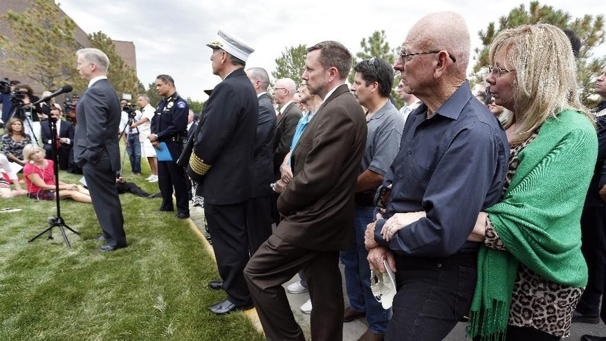 Lonnie, second from right, and Sandy Phillips, right, whose daughter Jessica Ghawi was killed in the 2012 Aurora movie theatre attack, hold each other as they listen to District Attorney George Brauchler, left, speak with members of the media after a jury failed to agree on whether theater shooter James Holmes should get the death penalty Friday, Aug. 7, 2015, in Centennial, Colo. Holmes will be sentenced to life in prison without parole. (AP Photo/Brennan Linsley)