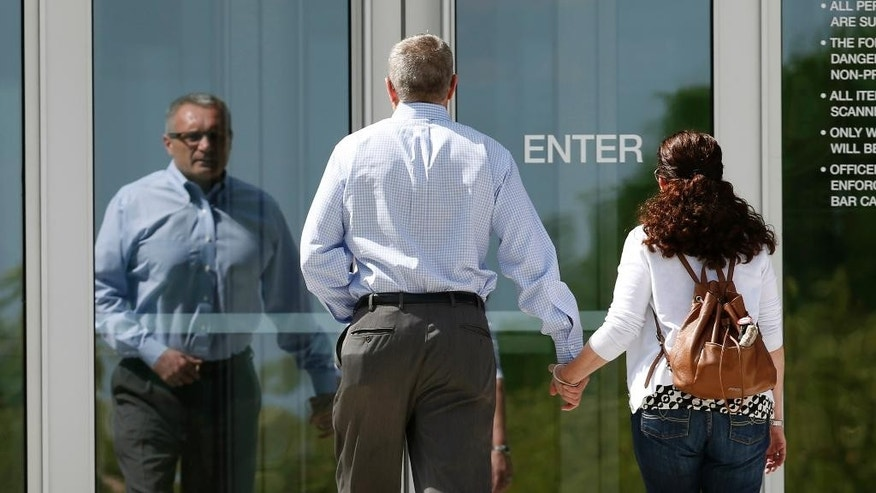 Tom, left, and Caren Teves, who lost their son, Alex, in the massacre at a movie theater in Aurora, Colo., in July 2012, head into the Arapahoe County Courthouse to hear the verdict reached in the penalty phase of the trial of convicted shooter James Holmes Friday, Aug. 7, 2015, in Centennial, Colo. Jurors have reached a decision on whether to sentence Holmes to life in prison or the death penalty. (AP Photo/David Zalubowski)