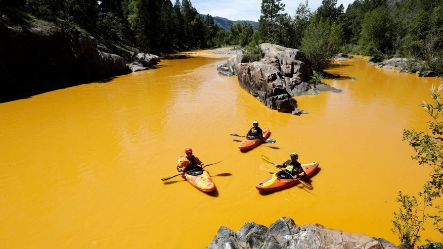 Aug. 6, 2015: People kayak in the Animas River near Durango, Colo. in water colored from a mine waste spill.