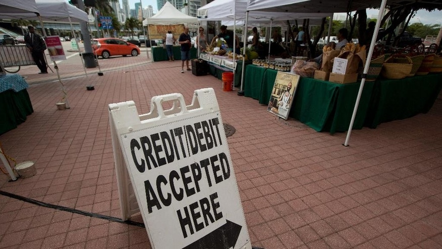 In this June 8, 2015 photo, credit card customers are directed to a pay station at the green market in downtown Miami. The Federal Reserve releases consumer credit data for June on Friday, Aug. 7, 2015. (AP Photo/J Pat Carter)