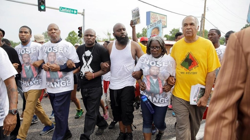 Michael Brown Sr., center, locks arms with others as he takes part in a parade in honor of his son, Michael Brown, Saturday, Aug. 8, 2015, in Ferguson, Mo. Sunday will mark one year since  Brown was shot and killed by Ferguson police officer Darren Wilson. (AP Photo/Jeff Roberson)