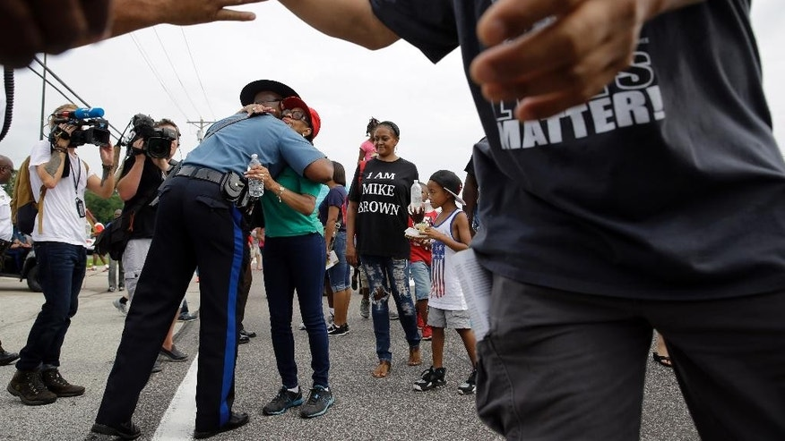 Missouri Highway Patrol Capt. Ron Johnson, left, gets a hug from a person participating in a parade in honor of Michael Brown Saturday, Aug. 8, 2015, in Ferguson, Mo. Sunday will mark one year since Michael Brown was shot and killed by Ferguson police officer Darren Wilson. (AP Photo/Jeff Roberson)