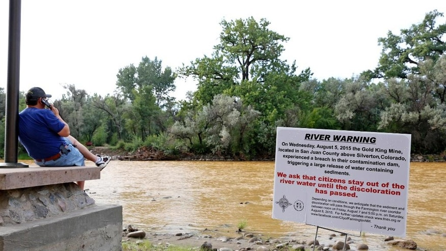 A warning sign from the city is displayed in front of the Animas River as orange sludge from a mine spill upstream flows past Berg Park in Farmington, N.M., Saturday, Aug. 8, 2015. About 1 million gallons of wastewater from Colorado's Gold King Mine began spilling into the Animas River on Wednesday when a cleanup crew supervised by the Environmental Protection Agency accidentally breached a debris dam that had formed inside the mine. The mine has been inactive since 1923. (Alexa Rogals/The Daily Times via AP)