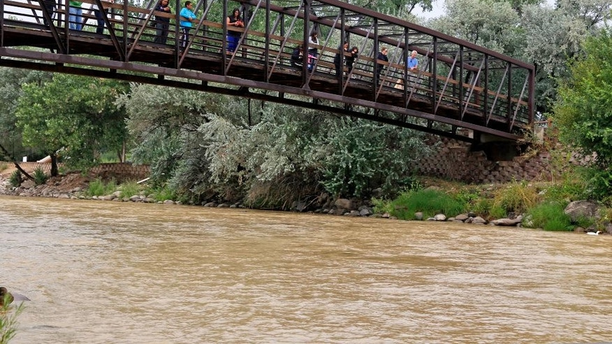 Onlookers view the Animas River from a bridge as orange sludge from a mine spill upstream flows past Berg Park in Farmington, N.M., Saturday, Aug. 8, 2015. About 1 million gallons of wastewater from Colorado's Gold King Mine began spilling into the Animas River on Wednesday when a cleanup crew supervised by the Environmental Protection Agency accidentally breached a debris dam that had formed inside the mine. The mine has been inactive since 1923. (Alexa Rogals/The Daily Times via AP)