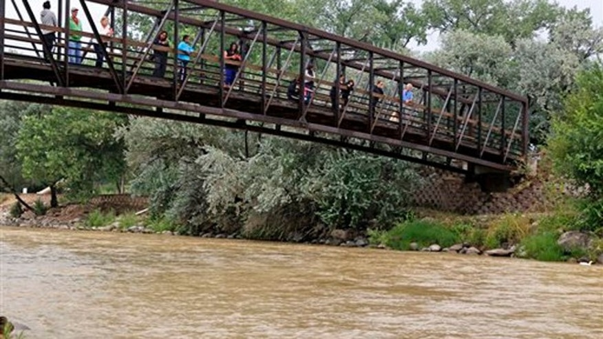 Aug. 8, 2015: Onlookers view the Animas River from a bridge as orange sludge from a mine spill upstream flows past Berg Park in Farmington, N.M.