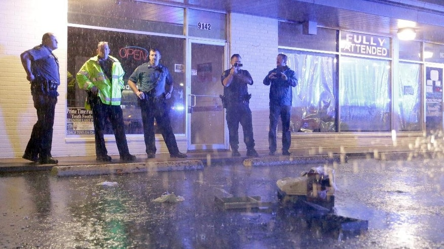 Police stand near a broken cash register in a parking lot after the front windows of a business were broken out along West Florissant Avenue, Sunday, Aug. 9, 2015, in Ferguson, Mo. Sunday marks one year since Michael Brown was shot and killed by Ferguson police officer Darren Wilson. (AP Photo/Jeff Roberson)