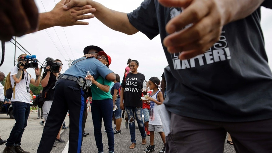 Aug. 8, 2015: Missouri Highway Patrol Capt. Ron Johnson, left, gets a hug from a person participating in a parade in honor of Michael Brown in Ferguson, Mo.