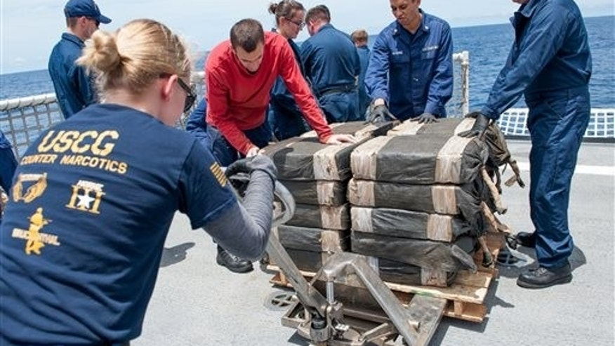 In this July 19, 2015 photo released by the U.S. Coast Guard, Coast Guard Cutter Stratton crew members secure cocaine bale from a self-propelled semi-submersible in international waters off the coast of Central America. The seizure of around 12,000 pounds was one of the largest busts of its kind.