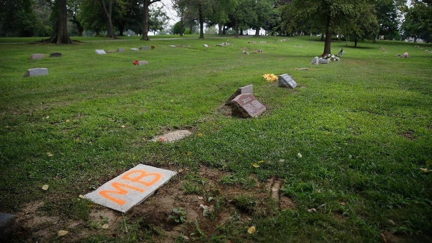 "The gravesite of Michael Brown, bottom left, is marked with a piece of stone with ""MB"" painted on it inside St. Peter's Cemetery Sunday, Aug. 9, 2015, in Normandy, Mo. Sunday marks one year since Brown was shot and killed by Ferguson police officer Darren Wilson. (AP Photo/Jeff Roberson)"
