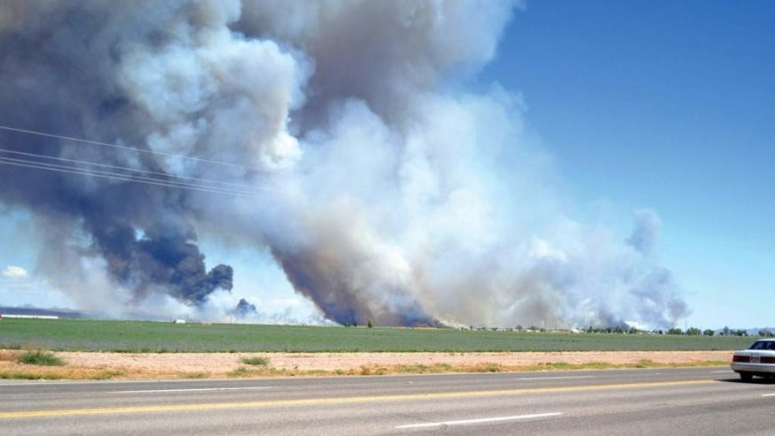 In this Saturday, Aug. 8, 2015 photo, smoke billows over Topock Marsh in the Mohave Valley south of Bullhead City, Ariz. Worsening conditions at the wildfire have prompted authorities to issue a second evacuation order this weekend. (Bill McMillen/Mohave Valley Daily News via AP) MANDATORY CREDIT