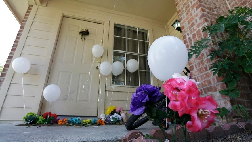 Flowers and eight balloons are seen at a house, Sunday, Aug. 9, 2015, where eight people were killed on Saturday in Houston. A family of six children and two parents were handcuffed and fatally shot in the head at a Houston home by a man with a violent criminal history who had previously been in a relationship with the mother and had a dispute with her, authorities said Sunday. David Conley, 48, was charged with capital murder in the deaths. (AP Photo/David J. Phillip)