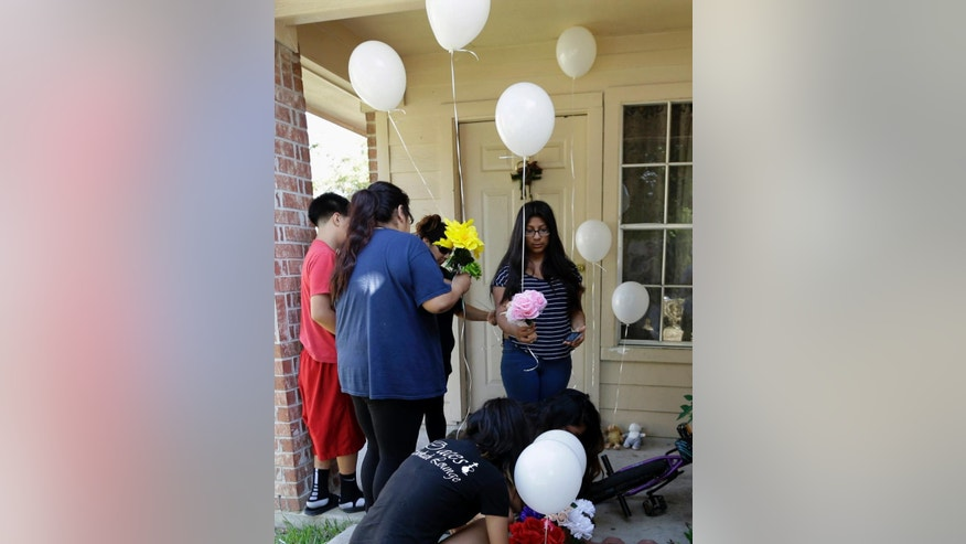 People place flowers and balloons at a house, Sunday, Aug. 9, 2015, where eight people were killed on Saturday in Houston. A family of six children and two parents were handcuffed and fatally shot in the head at a Houston home by a man with a violent criminal history who had previously been in a relationship with the mother and had a dispute with her, authorities said Sunday. David Conley, 48, was charged with capital murder in the deaths. (AP Photo/David J. Phillip)