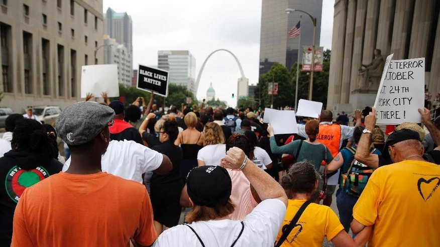 Protesters march to the Thomas F. Eagleton Federal Courthouse, Monday, Aug. 10, 2015, in St. Louis. Several protesters were arrested after arriving at the courthouse. (AP Photo/Jeff Roberson)