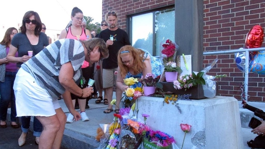 People place flowers, Sunday, Aug. 9, 2015, at the site where Vermont social worker Lara Sobel was killed on Friday in Barre, Vt. About 300 people attended a vigil that began at a labor hall and ended at the site where Sobel was shot Friday as she left work. Jody Herring, the woman charged with Sobel's death, is due in court Monday. (AP Photo/Wilson Ring)