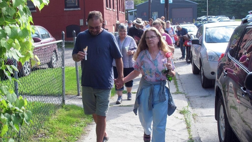Joe Faryniarz, left, and Tiertza-Leah Schwartz, cousins of slain Vermont social worker Lara Sobel, lead a procession in her memory, Sunday, Aug. 9, 2015, in Barre, Vt. About 300 people attended a vigil that began at a labor hall and ended at the site where Sobel was shot Friday as she left work. Jody Herring, the woman charged with Sobel's death, is due in court Monday. (AP Photo/Wilson Ring)