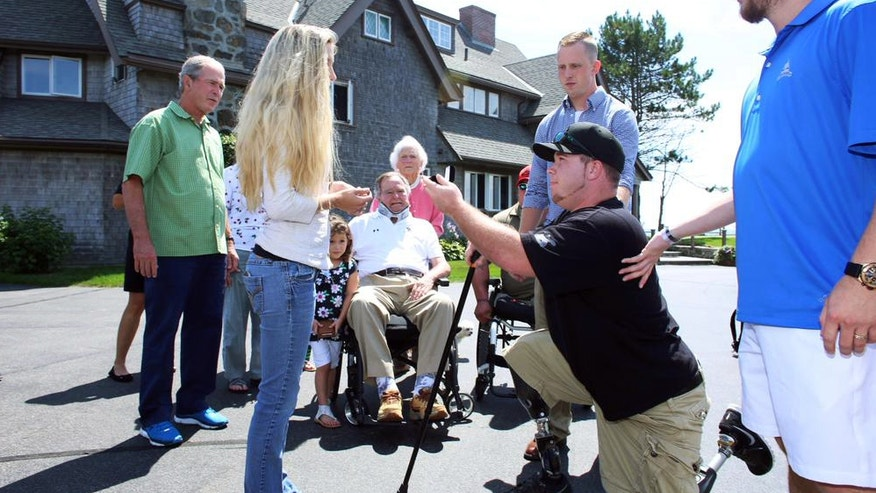 In this Monday, Aug. 10, 2015 photo provided by the office of former President George H.W. Bush, Army Spc. Tyler Jeffries proposes to Lauren Lilly at the Bush summer home in Kennebunkport, Maine. Former Presidents George H.W. Bush, his son George W. Bush and their first ladies witnessed the proposal. (Office of George H.W. Bush via AP)