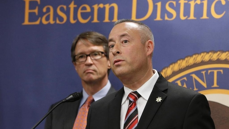 Frank Alvarez, right, chief investigator for the Department of Motor Vehicles, responds to a question concerning a federal investigation of a scheme where as many as 100 commercial truck drivers paid up to $5,000 to DMV employees for illegal California licenses, Tuesday, Aug. 11, 2015, in Sacramento,Calif.  Court records say that three DMV employees, two in Salinas and one in Sacramento, changed computer records to falsely show that drivers passed written and behind-the-wheel tests. The owners of three truck driving schools have also been charged with conspiracy to commit bribery and to commit identity fraud.  At left is Benjamin B. Wagner, United State Attorney of the Eastern District of California.(AP Photo/Rich Pedroncelli)