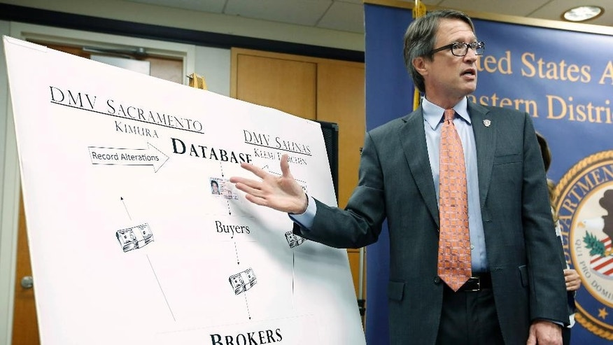 Benjamin B.Wagner, United States Attorney for the Eastern District of California, gestures to a chart showing how California Department of Motor Vehicle employees were bribed for providing fraudulent California licenses to commercial truck drivers, Tuesday, Aug. 11, 2015, in Sacramento,Calif.  Wagner said that three DMV employees, two in Salinas and one in Sacramento,  were paid up to $5,000 to change computer records to falsely show that drivers passed written and behind-the-wheel tests. The owners of three truck driving schools have also been charged with conspiracy to commit bribery and to commit identity fraud.  (AP Photo/Rich Pedroncelli)