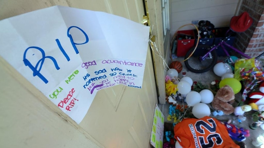 A sign hangs on the door Monday, Aug. 10, 2015, as part of the condolences left outside the home where eight people were shot over the weekend in Houston. David Conley, who has a violent criminal history, entered the Houston home through an unlocked window and fatally shot a woman he'd previously dated, her husband and six children, including a boy believed to be his own son, authorities said. He is charged with capital murder in the deaths (AP Photo/David J. Phillip)