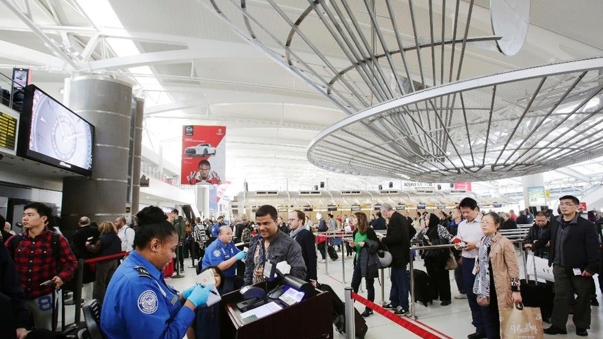 FILE - In this Oct. 30, 2014, file photo, a TSA officer, left, checks a passenger's ticket, boarding pass and passport as part of security screening at John F. Kennedy International Airport in New York. A court challenge over the difficulty for airline passengers to remove their names from the U.S. government's no-fly list is taking an unexpected twist, now focusing on the mysterious ways federal agents add passenger names to the list in the first place.  (AP Photo/Mark Lennihan, File)