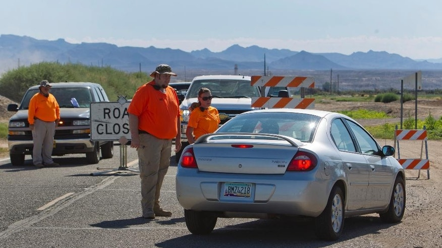 Mohave Valley Search and Rescue volunteer Chris Lyons, center, talks to a motorist at a road closure in Mohave Valley, Ariz. Monday, Aug. 10, 2015. Most areas around the Willow Fire are still restricted. Eleven homes are reported to have been destroyed in the blaze. (Steve Marcus/Las Vegas Sun via AP) LAS VEGAS REVIEW-JOURNAL OUT; MANDATORY CREDIT