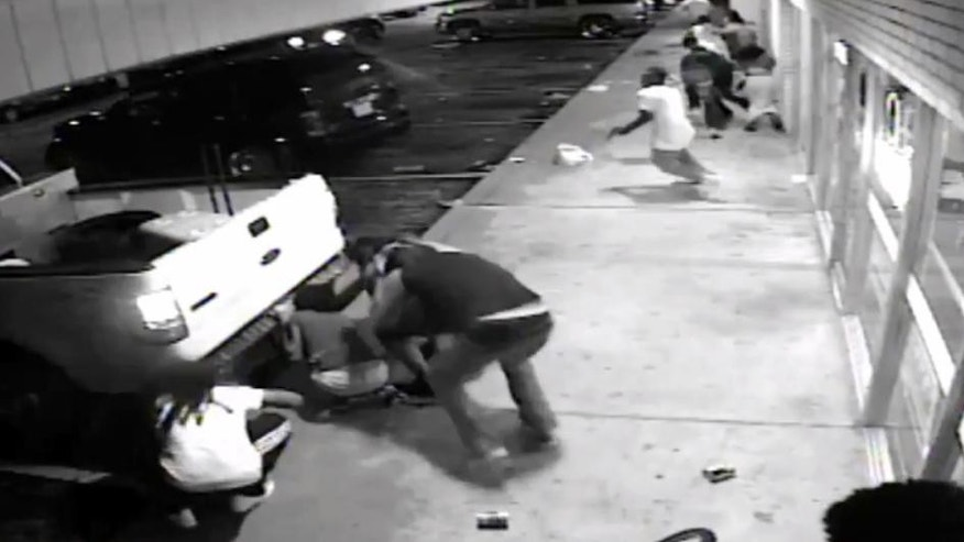 In this Aug. 9, 2015, frame from surveillance video provided by the St. Louis County Police shows the 18-year-old black suspect, center in light colored clothes, minutes before he fired a gun at plainclothes officers, according to police in Ferguson, Mo. Tyrone Harris Jr. was shot late Sunday after police say he opened fire on an unmarked police van. The shooting happened as protesters nearby were marking the anniversary of the shooting death of Michael Brown, who was killed by a white police officer. (St. Louis County Police via AP)