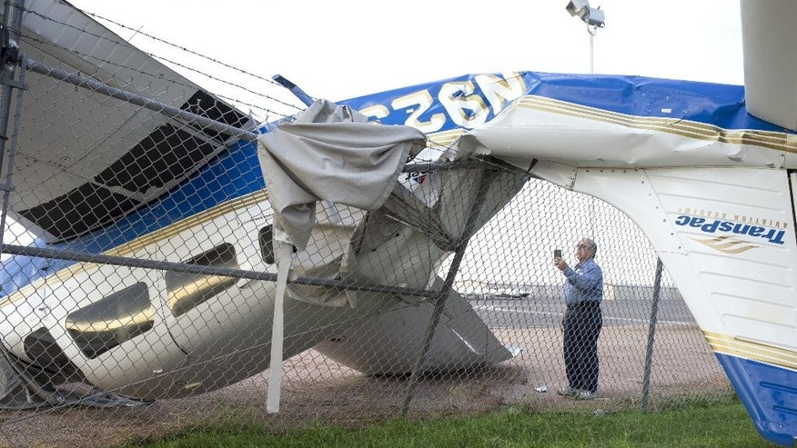 A TransPac employee checks a damaged plane, Wednesday, Aug. 12, 2015, at Chandler Municipal Airport in Chandler, Ariz. At least a dozen small planes were heavily damaged after a monsoon storm swept into the Phoenix area Tuesday night.   (Mark Henle/The Arizona Republic via AP)  MARICOPA COUNTY OUT; MAGS OUT; NO SALES; MANDATORY CREDIT
