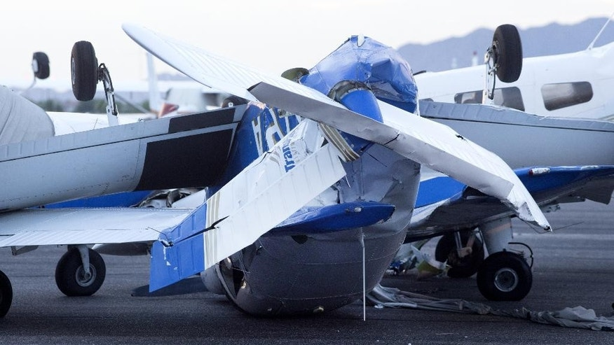 A plane is upended at Chandler Municipal Airport, Wednesday, Aug. 12, 2015, in Chandler, Ariz. At least a dozen small planes were heavily damaged after a monsoon storm swept into the Phoenix area Tuesday night.   (Mark Henle/The Arizona Republic via AP)  MARICOPA COUNTY OUT; MAGS OUT; NO SALES; MANDATORY CREDIT