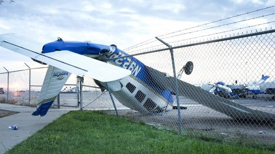 A plane is upended onto a fence at Chandler Municipal Airport, Wednesday, Aug. 12, 2015, in Chandler, Ariz. At least a dozen small planes were heavily damaged after a monsoon storm swept into the Phoenix area Tuesday night.   (Mark Henle/The Arizona Republic via AP)  MARICOPA COUNTY OUT; MAGS OUT; NO SALES; MANDATORY CREDIT