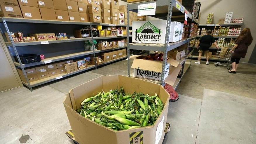 In this July 29, 2015 photo, a load of sweet corn sits ready to be given away at the Des Moines Area Religious Council food pantry in Des Moines, Iowa. Food banks across the country are seeing surging demand for free groceries despite a growing economy and steadily declining unemployment rate, leading some charities to reduce the amount of food they offer each family. (AP Photo/Charlie Neibergall)