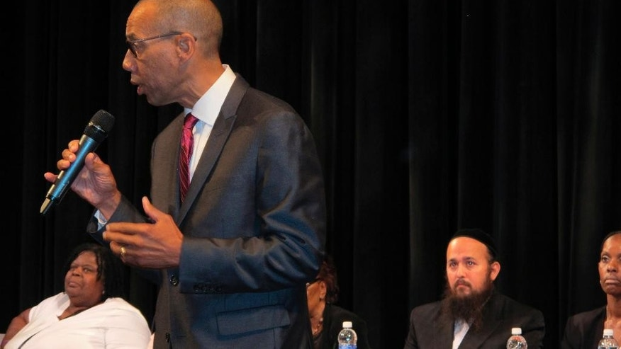 Former New York City Schools Chancellor Dennis Walcott addresses a community meeting in Suffern, N.Y., on Thursday, Aug. 13, 2015, after being appointed monitor in the East Ramapo school district. Walcott will examine a bitter dispute between the school board, which is dominated by Orthodox Jews who don't use the public schools, and the mostly black or Hispanic families with students in the public school families. Behind Walcott, are, left to right, state Regent Josephine Finn, school board President Yehuda Weissmandl and Monica George-Fields, who will assist Walcott. (AP Photo/Jim Fitzgerald).