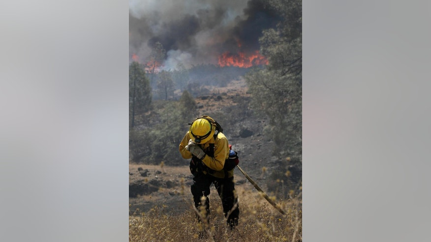 Garden Valley firefighter Chris Schwegler carries a hose as fires burn near Lower Lake, Calif., Thursday, Aug. 13, 2015. Crews battling the wind-stoked blaze took advantage of cooler temperatures Thursday to clear brush and expand containment lines with bulldozers and hand tools. (AP Photo/Jeff Chiu)