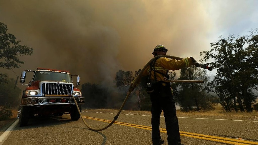 A firefighter holds a hose while watching a fire burning along Morgan Valley Road near Lower Lake, Calif., Thursday, Aug. 13, 2015. Crews battling the wind-stoked blaze took advantage of cooler temperatures Thursday to clear brush and expand containment lines with bulldozers and hand tools. (AP Photo/Jeff Chiu)