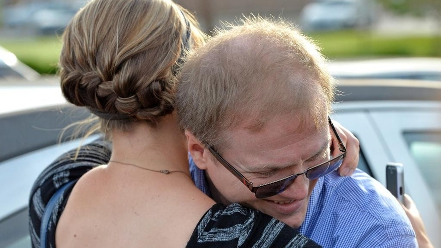 David Ermold, right, is hugged by Taral Thompson following the refusal of the Rowan County clerk's office to issue a marriage license to he and his partner, in defiance of a federal judge's decision in Morehead, Ky., Thursday, Aug. 13, 2015. Rowan County Clerk Kim Davis has already filed a notice of appeal and plans to request a stay on the ruling. (AP Photo/Timothy D. Easley)
