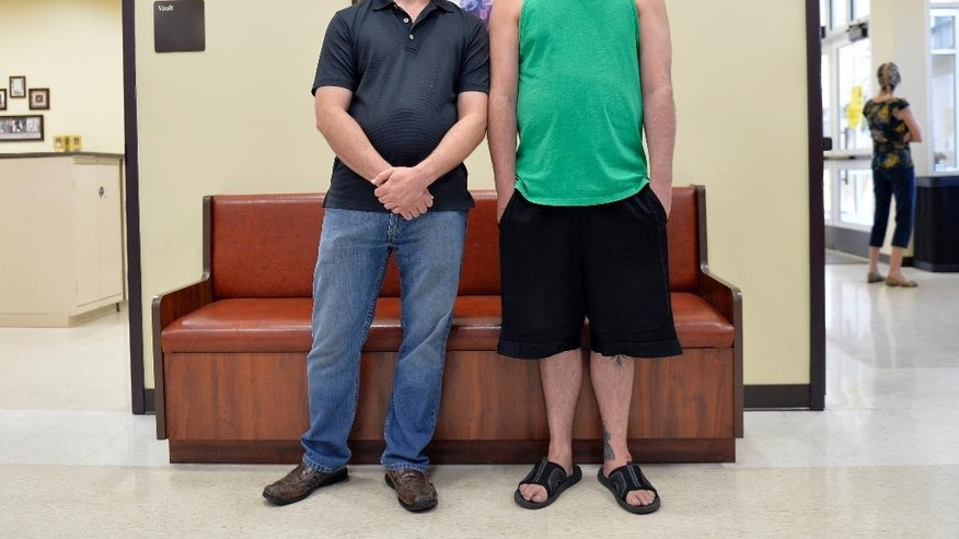 James Yates, left, and William Smith Jr. wait in line at the Rowan County Clerks Office to obtain a marriage license in Morehead, Ky., Thursday, Aug. 13, 2015. In a decision on Wednesday, U.S. District Judge David L. Bunning ordered Rowan County Clerk Kim Davis to issue marriage licenses to all couples, but she has refused after filing an appeal to the ruling to the Sixth Circuit Court of Appeals. (AP Photo/Timothy D. Easley)