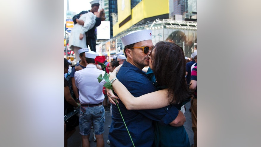 "Married couple Oscar Gifford, from New York, and Alessandra Ciani, right, from Palmanova, Italy, kiss before scores re-enact the iconic 1945 Alfred Eisenstaedt kiss photo, Thursday, Dec. 10, 2015, in New York's Times Square.  Dozens of couples gathered in New York's Times Square to re-enact a famous kiss that celebrated the end of World War II.  A 25-foot high sculpture replica of the original kiss, top rear left, entitled ""Embracing Peace"" is in Times Square until Sunday during the celebration.  (AP Photo/Bebeto Matthews)"