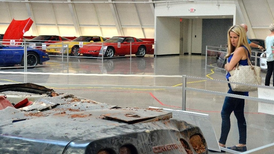 In this Wednesday, Aug. 12, 2015, photo, Stacy Jorgensen of Los Angeles, examines a display of the cars that were swallowed by the sinkhole at the National Corvette Museum in Bowling Green, Ky. The car-swallowing hole has been fixed but not forgotten at the museum. Yellow tape now marks the boundaries of the cavity that became a sensation and put the museum on the map. (AP Photo/Timothy D. Easley)