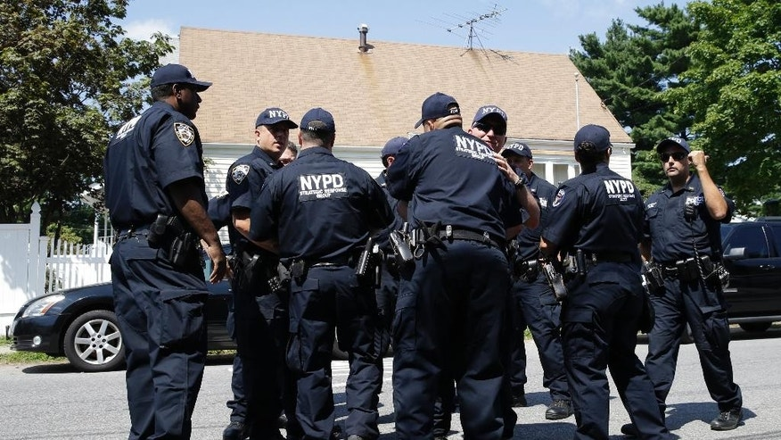 New York City police officers with the strategic response unit embrace as they leave the scene of a standoff, Friday, Aug. 14, 2015, in the Staten Island borough of New York. Garland Tyree, a high-ranking member of the Bloods street gang who was to be arrested on parole violations when he shot a firefighter responding to a call of smoke coming from his girlfriend's home, died Friday in a gunfight with police after a six-hour standoff, two police officials said.  (AP Photo/Mary Altaffer)