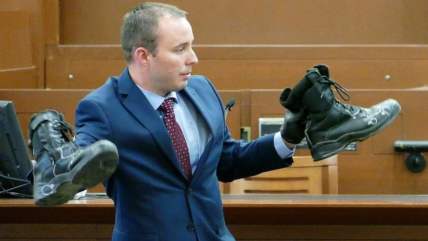 Charlotte-Mecklenburg police Officer Randall Kerrick Randall displays the boots he was wearing the night of the shooting during his voluntary manslaughter trial, Thursday, Aug. 13, 2015, in Charlotte, N.C. Kerrick charged in the shooting death of an unarmed black man has testified in his own defense Thursday, following witnesses who quoted him as saying he thought his life was in danger.  (Davie Hinshaw/The Charlotte Observer via AP, Pool)
