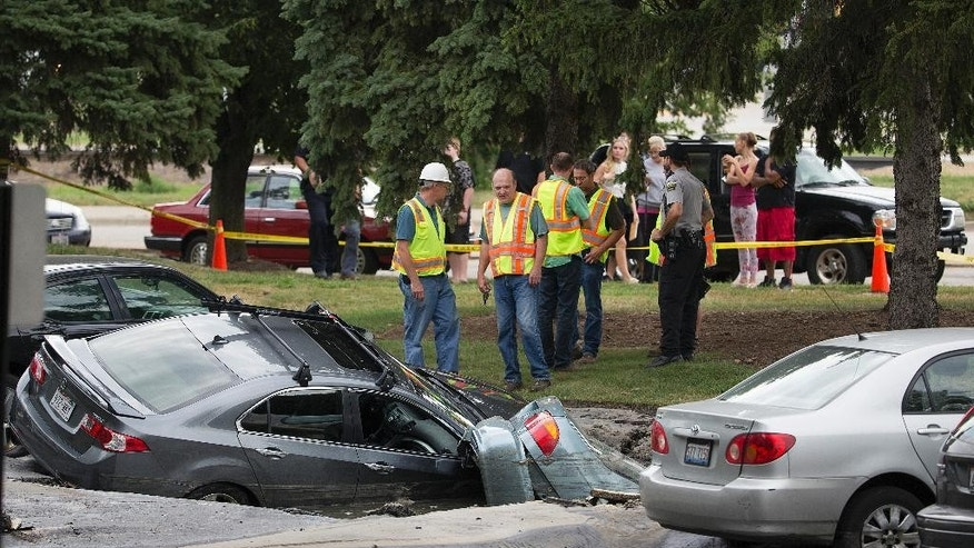 Cars are engulfed in a sinkhole at an apartment complex Friday, Aug. 14, 2015, in Madison, Wis. About 300 residents of the complex were evacuated after a water pipe break created a sinkhole and potential gas leak. (Steve Apps/Wisconsin State Journal via AP) MANDATORY CREDIT