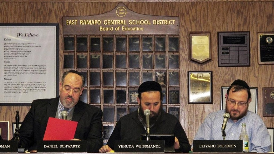 "FILE - In this March 19, 2013 file photo, members of the East Ramapo School Board  are seated at a table together during a school board meeting in in Spring Valley, N.Y. Allegations of racism and anti-Semitism are afflicting the district, where the board is dominated by ultra-Orthodox Jews and the public school children are mostly black and Hispanic. Newly appointed state monitor, former New York City Schools Chancellor Dennis Walcott, says he plans to go to ""barber shops, beauty parlors, hanging out on corners"" to find out more about the decade-long control of the public schools by ultra-Orthodox Jews, who do not use the public schools but have nevertheless made deep cuts in teachers and programs. From left are East Ramapo School Board President Daniel Schwartz and board members Yehuda Weissmandl and Eliyahu Solomon. (AP Photo/Jim Fitzgerald, File)"