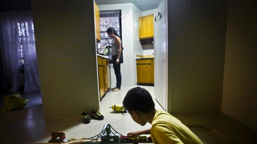 Domestic violence survivor K, left, her name withheld for confidentiality, prepares dinner for her son while he plays outside the kitchen doorway of their new apartment, Thursday, Aug. 13, 2015, in New York.  After leaving her husband who beat and controlled her for years, K and her little boy spent the next three years homeless because she couldn't afford New York City rents.  (AP Photo/Bebeto Matthews)