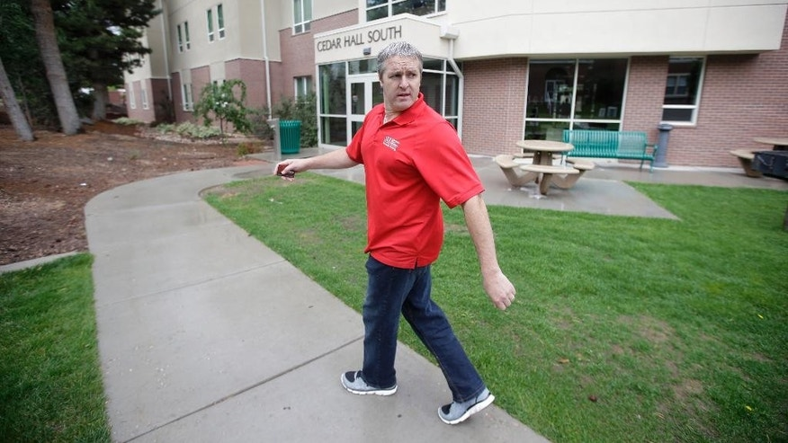 In this Friday, Aug. 7, 2015 photo, Southern Utah University's Chris Ralphs, director of university housing, walks outside of Cedar Hall South on the campus of Southern Utah University, in Cedar City, Utah. This fall, an enrollment boom that created a housing crisis is prompting Southern Utah University to urge neighbors and employees alike to house the dormless, including hundreds of incoming freshmen who wanted to live on campus. (AP Photo/Rick Bowmer)