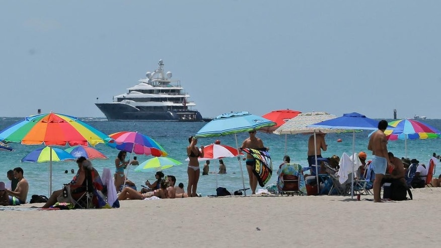 In this, Saturday, Aug. 8, 2015 photo, beach goers enjoy a day on the sand on South Beach, in Miami Beach, Fla. European visitation to Florida was up 6 percent from 2013 to 2014, the most recent totals available. About 4 million Europeans visited the state, according to Visit Florida, the state's tourism agency. Florida beach tourism leaders say they are getting a boost in European visitors this summer because of the turmoil in Greece and the Middle East. (AP Photo/Wilfredo Lee)