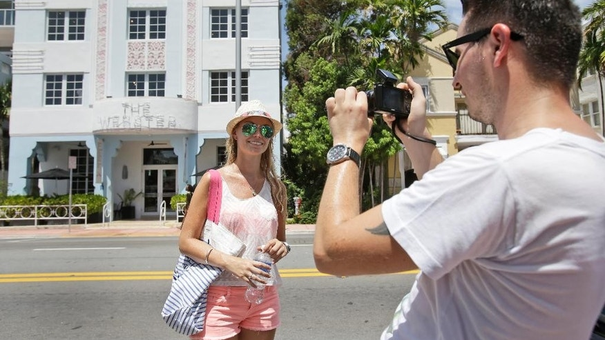 In this, Saturday, Aug. 8, 2015 photo, Nina Rysterborgh, 26, center, and John Snackers, 31, a couple from Holland, the Netherlands, take photos as they take a walking tour of Art Deco buildings in South Beach, in Miami Beach, Fla. European visitation to Florida was up 6 percent from 2013 to 2014, the most recent totals available. About 4 million Europeans visited the state, according to Visit Florida, the state's tourism agency. Paul Phipps, Visit Florida's marketing director, expects the trend to continue. (AP Photo/Wilfredo Lee)