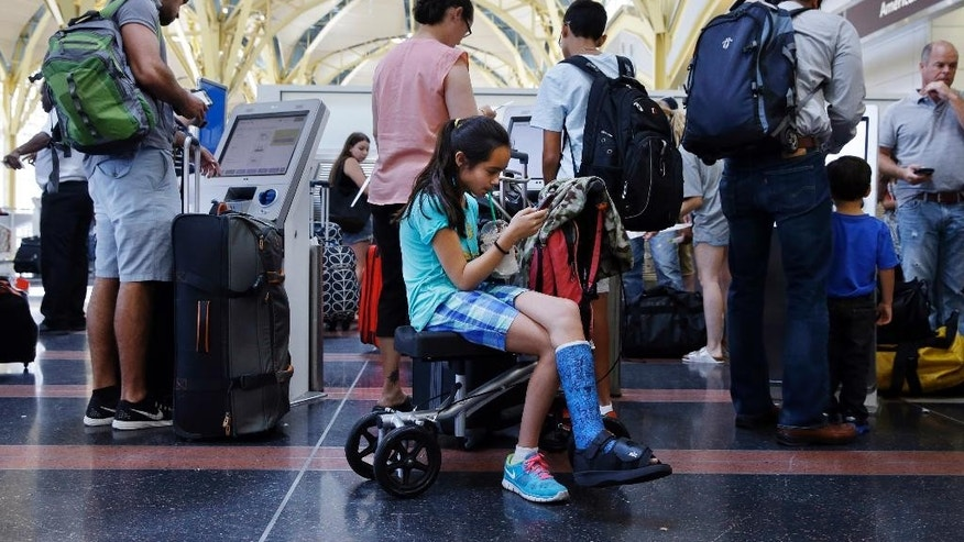 After standing in line with for an hour and a half, Alisha Lalani, 10, of Ft. Lauderdale, Fla., looks at her phone as her mother and brother check in for their flight to Miami at Washington's Reagan National Airport, as technical issues at a Federal Aviation Administration center in Virginia caused delays on Saturday, Aug. 15, 2015. (AP Photo/Jacquelyn Martin)