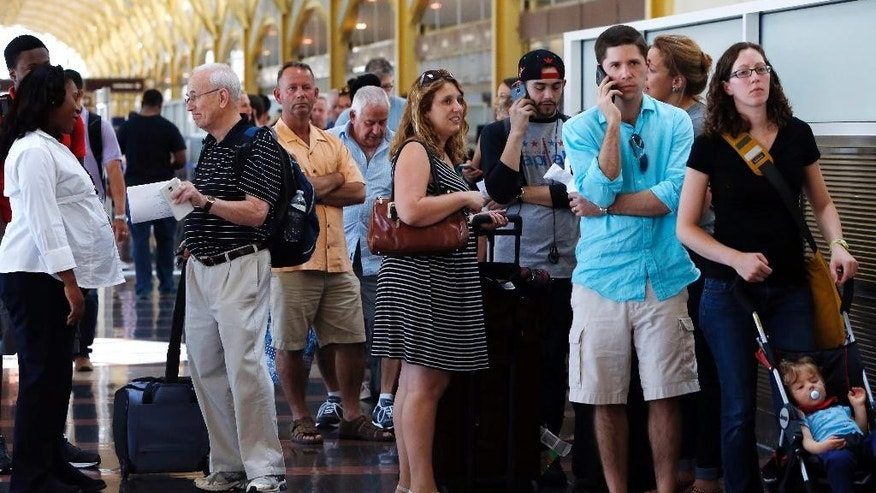 People stand in line at Washington's Reagan National Airport after technical issues at a Federal Aviation Administration center in Virginia caused delays on Saturday, Aug. 15, 2015. (AP Photo/Jacquelyn Martin)